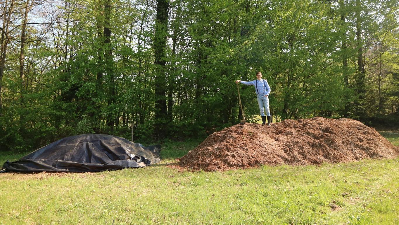 Ob kompostnem kupu je tudi velik kup lesnih sekancev. Prav tako za vrt. Kompost priprava.